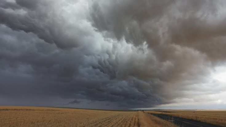 A storm cloud looms over a field