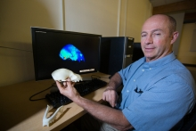 Ian Grosse holding animal skull in front of computer screen with 3d image of same animal skull